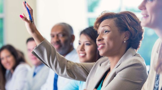 woman raising her hand at a meeting